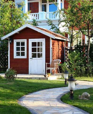 花园的入口是白色的欧式木门,随着石板路以及各种花草便延伸进