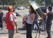 女记者戴墨镜打伞采访救灾志愿者 被电视台停职