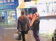 高三男生为打车残疾人撑伞 帮助其回家